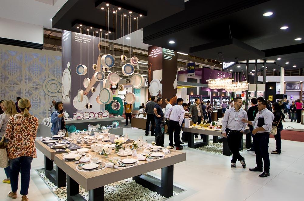 Stand da Oxford Porcelanas na 52ª Gift Fair. Nas primeiras mesas, temos os lustres com a Moon, nova linha de pratos em porcelana. E ao fundo da foto podemos ver os lustres com taças de cristal. Foto: Henrique Perón.