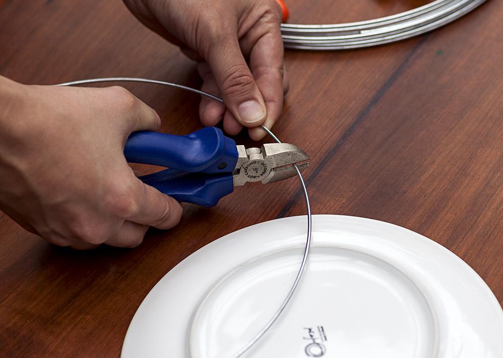 """Imagem: Passo 2: Corte 1/3 do arame que você obteve medindo a circunferência do prato e, com esta parte (a menor), faça a haste inferior do suporte, dobrando levemente o centro da haste, até formar um """"V"""" mais aberto. Foto: Raphael Günther/Bespoke Content."""