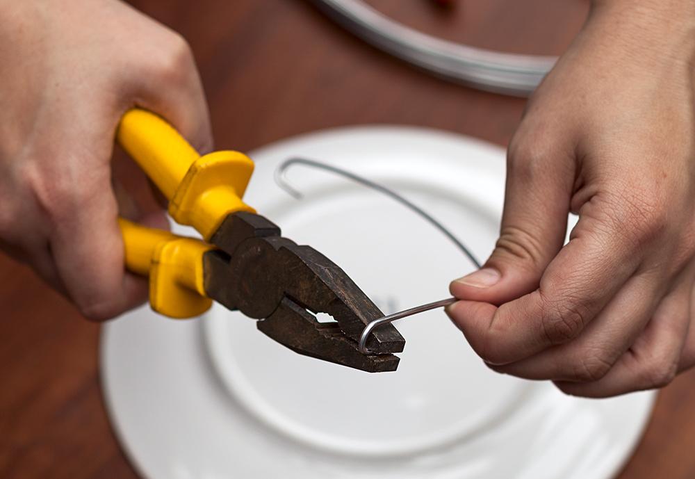 Imagem: Passo 3: Na sequência, dobre as duas pontas do arame em V conforme a espessura do prato, fixando esta haste na parte inferior da louça. Foto: Raphael Günther/Bespoke Content.