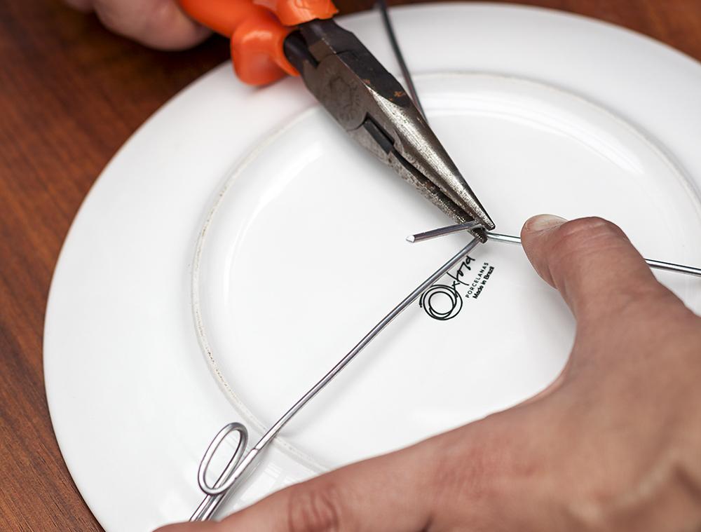 Imagem: Passo 7: Firmando bem com os dedos, dobre o arame para cima o mais apertado possível, garantindo assim a sustentação perfeita. Corte os excessos. Foto: Raphael Günther/Bespoke Content.