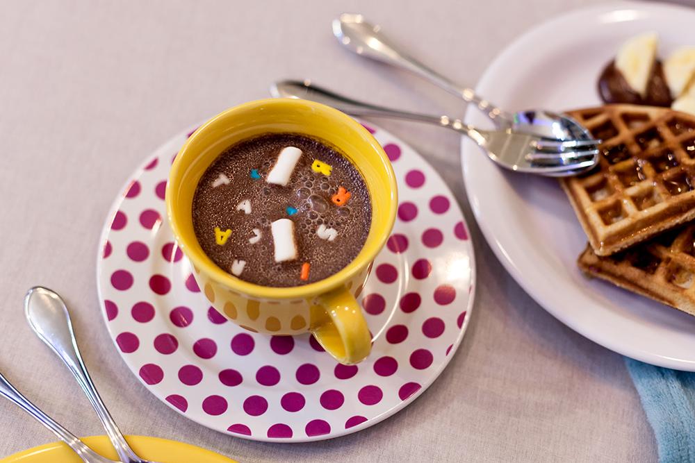 Imagem: Delícia de chocolate quente numa combinação de louças inusitada e fofa: xícara da coleção Floreal Yellow com o pratinho do Conjunto para Bolo Dots. Foto: Raphael Günther/Bespoke Content.