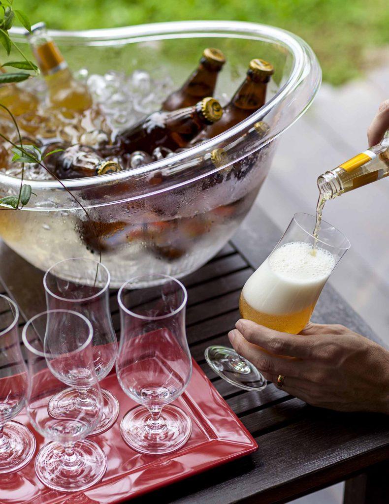Imagem: E tem coisa melhor que uma cerveja bem gelada para espantar o calor? E para ela não esquentar antes de acabar, a dica é um balde transparente de tamanho generoso, que além de suprir a necessidade de uma festa, funciona como objeto decorativo. Isso sem falar que deixa as bebidas à mostra, facilitando a escolha. E não se esqueça de investir em copos de cerveja. Foto: Raphael Günther/Bespoke Content.