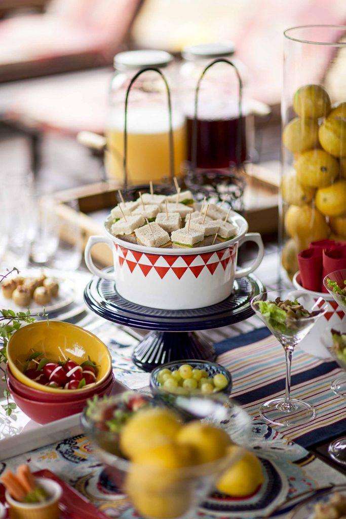 Imagem: Para ganhar espaço na mesa principal, os mini sanduíches frios foram sobrepostos em uma sopeira. A louça foi disposta sobre um prato de bolo para ganhar mais destaque na mesa. Foto: Raphael Günther/Bespoke Content.