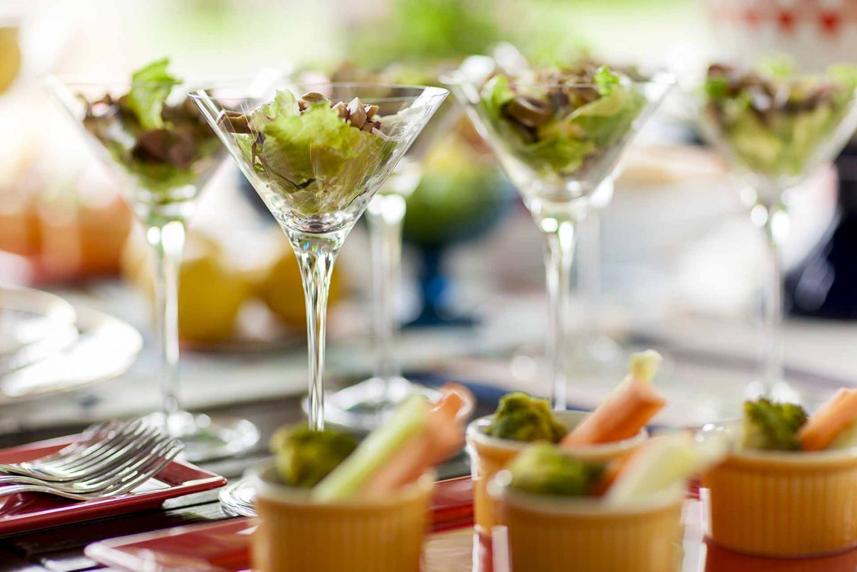 Imagem: Servir em pequenas porções de comida é o ideal para deixar esse tipo de evento mais descontraído. Aqui, as saladas ganharam destaque em taças de Martini e com molhos servidos à parte. Foto: Raphael Günther/Bespoke Content.