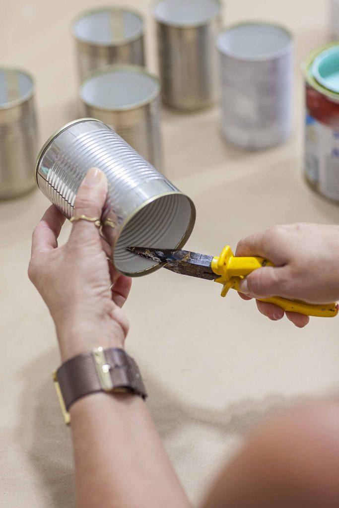 Imagem: Passo 1: Com o auxílio de um alicate, dobre as rebarbas que tenham ficado no interior das latas. Se preferir, lixe com uma lima. Foto: Raphael Günther/Bespoke Content.