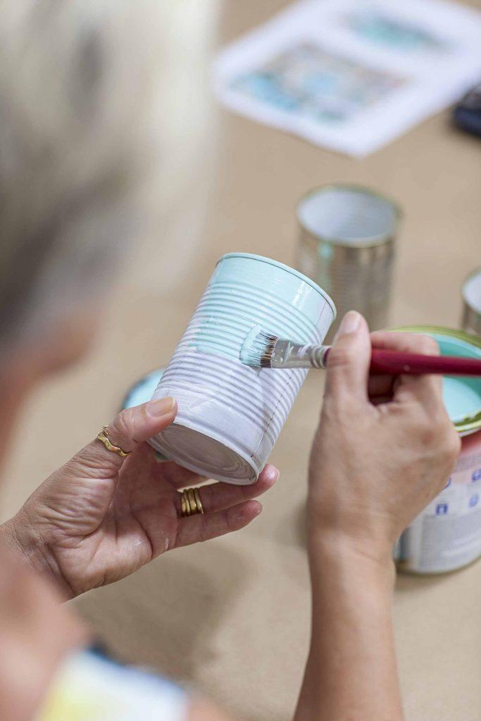 Imagem: Passo 2: Retire as sobras de cola do rótulo com solvente. Para melhor fixação da tinta, passe o primer para metal na parte de fora das latas. Em seguida, pinte as latas por dentro e por fora com tinta esmalte sintético na cor de sua preferência e deixe secar bem. Repita o processo com a madeira, mas sem usar o primer. Foto: Raphael Günther/Bespoke Content.