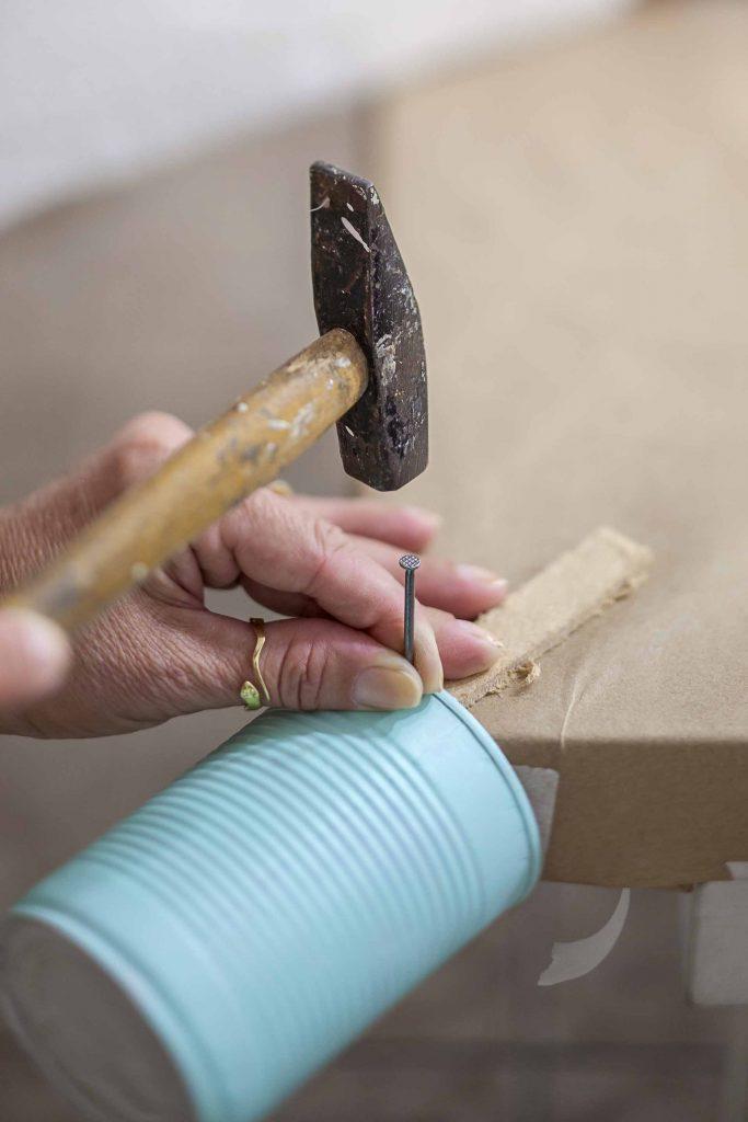 Imagem: Passo 3: Com um prego grosso e um martelo, faça um furo na lata para, em seguida, colocar o parafuso. Utilize o canto da mesa para facilitar e, com a ajuda de uma madeira, apoie a lata em cima. Pode martelar com força que a lata não vai entortar. Para não machucar a pintura, coloque um pedaço de feltro entre a madeira e a lata. Foto: Raphael Günther/Bespoke Content.