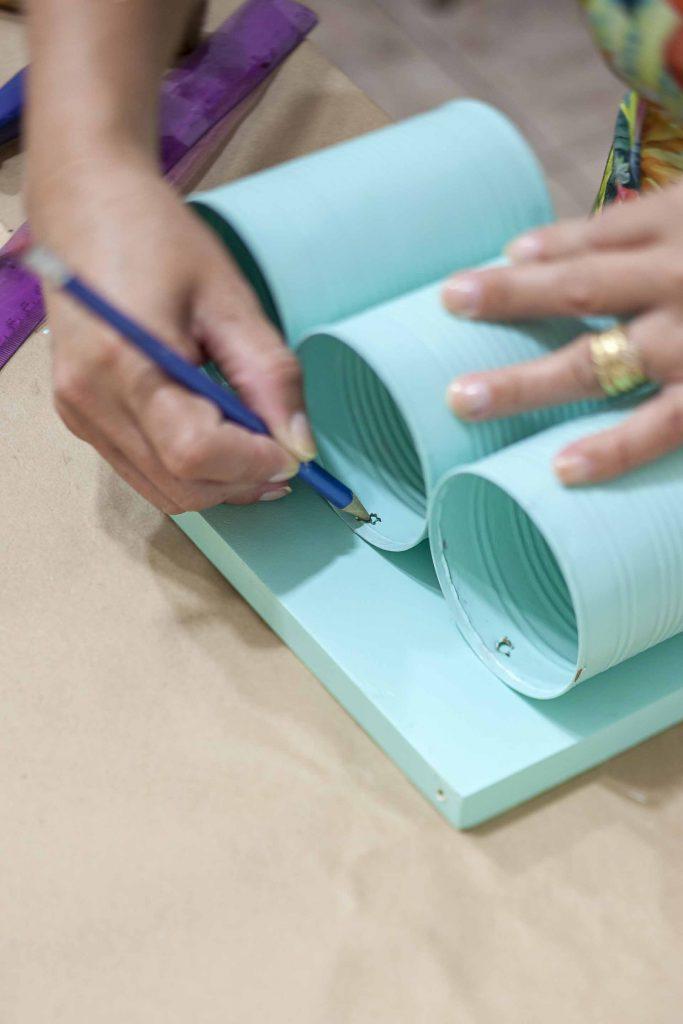 Imagem: Passo 4: Posicione as latas furadas no local que serão parafusadas. Marque o local do furo na madeira com uma lapiseira ou caneta. Foto: Raphael Günther/Bespoke Content.