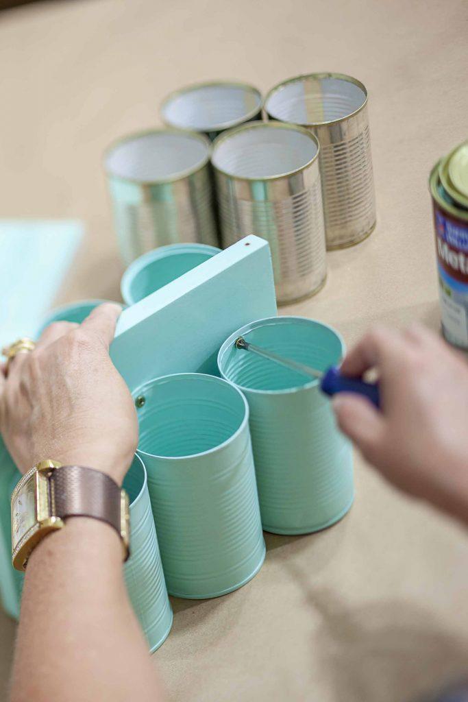 Imagem: Passo 6: Parafuse as latas na madeira. Foto: Raphael Günther/Bespoke Content.