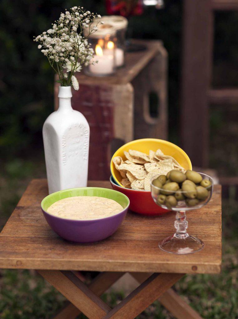 Imagem: Os bowls e as taças, ganhando uma nova função, facilitam a ideia de servir os petiscos fora da mesa principal. As tortillas de milho podem ser deliciosamente mergulhadas no molho de cheddar picante. Uma combinação ardente e irresistível. Foto: Raphael Günther/Bespoke Content.