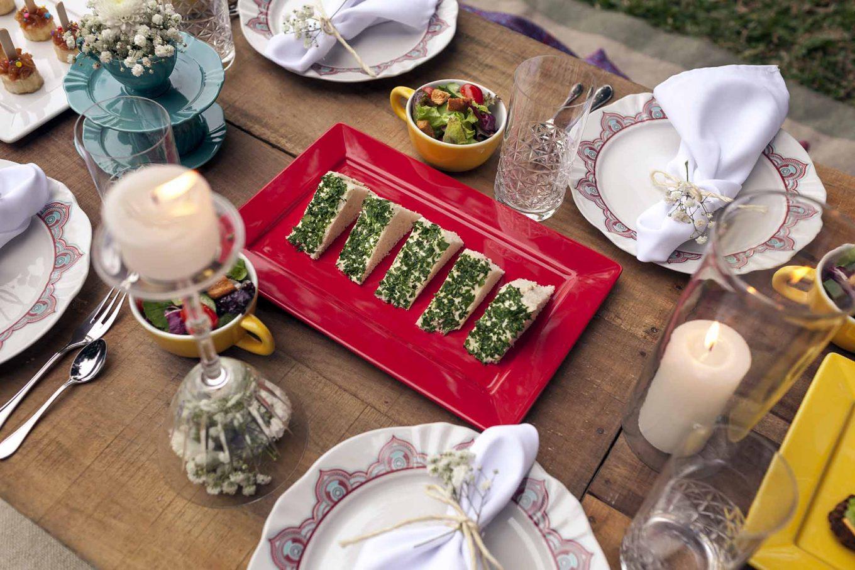 Imagem: Na mesa, foram escolhidos pratos e louças claras para criar uma harmoniosa brincadeira com peças coloridas. O prato vermelho contrasta com o verde da salsa e dá destaque ao branco do pão, deixando tudo mais apetitoso aos olhos. O sanduíche de atum é uma opção tradicional que agrada aos mais variados gostos. Foto: Raphael Günther/Bespoke Content.