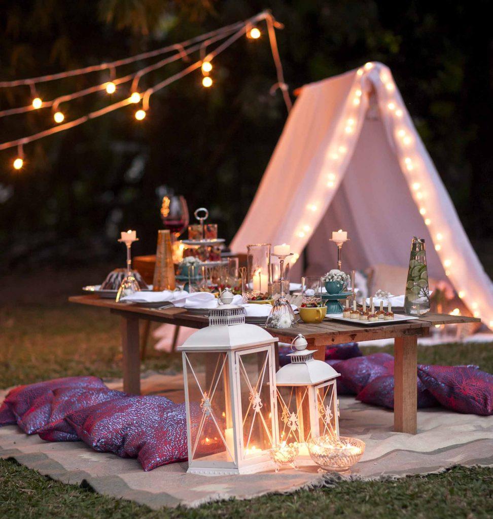 Imagem: As luzes, lanternas e velas ditam o clima da noite com muito romantismo, para que todos possam se aconchegar em um ambiente informal. Foto: Raphael Günther/Bespoke Content.