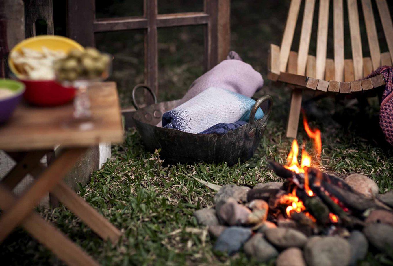 Imagem: Em noites frias, nada mais agradável do que se aquecer ao redor de uma fogueira e se aconchegar com mantinhas. Por isso, elas foram dispostas ao lado da fogueira, para que até quem sente mais frio possa curtir a noite ao ar livre. Foto: Raphael Günther/Bespoke Content.