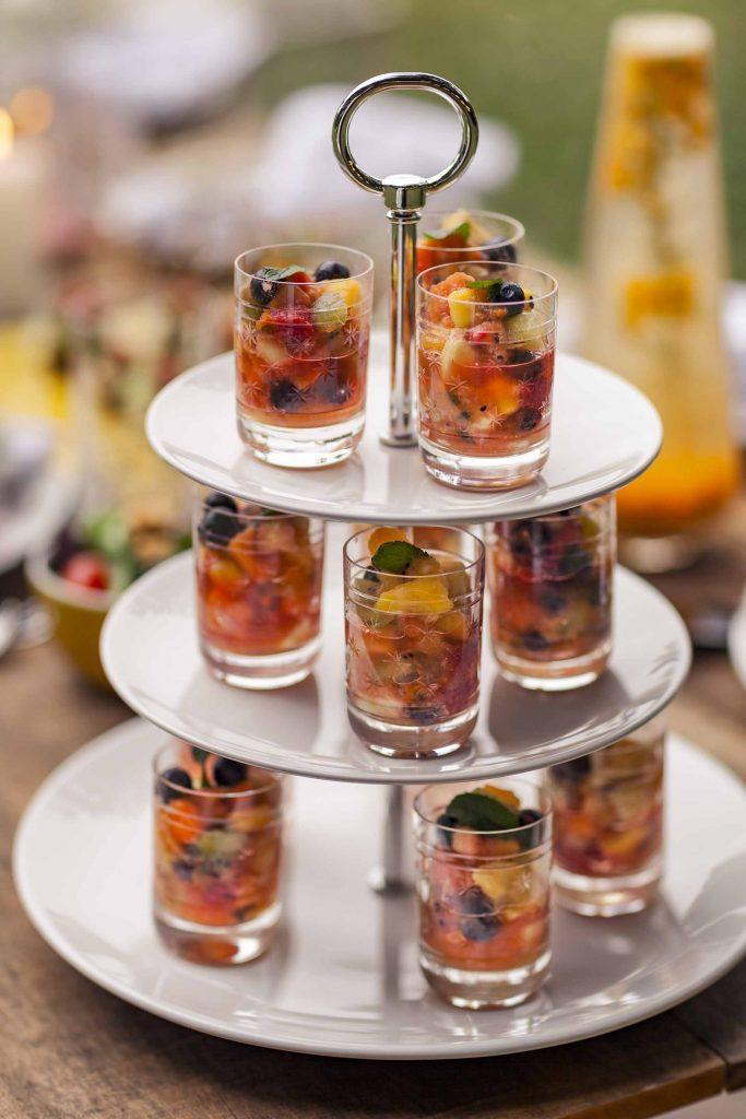 Imagem: Para uma opção saudável de sobremesa, foram escolhidas frutas nobres e refrescantes, servidas de forma criativa: dentro de copos de cachaça, em um lindo suporte para dar mais altura e profundidade à mesa. Foto: Raphael Günther/Bespoke Content.