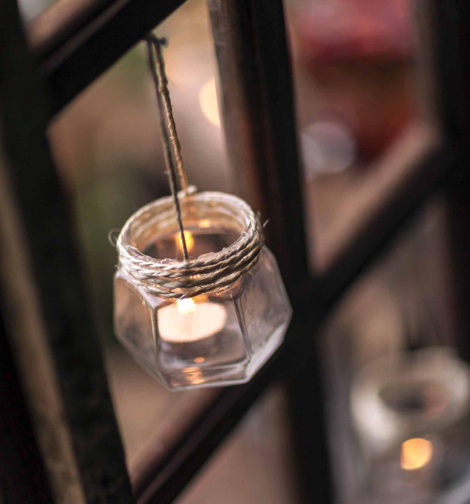 Imagem: Para criar um clima romântico e intimista, velas foram colocadas dentro de vidros reciclados e penduradas nesta janela antiga. Um encanto, não é mesmo? Foto: Raphael Günther/Bespoke Content.