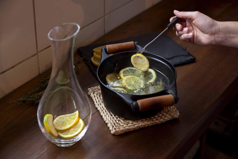 Imagem: Passo 3: Com a ajuda de um garfo, ou de um pegador, acomode as rodelas de limão e os ramos de alecrim no recipiente. Foto: Raphael Günther/Bespoke Content.