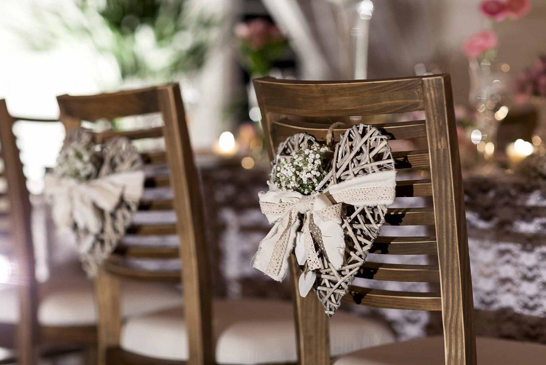 Imagem: As cadeiras dos noivos foram marcadas com corações de vime e detalhes em renda e algodão. Foto: Raphael Günther/Bespoke Content.