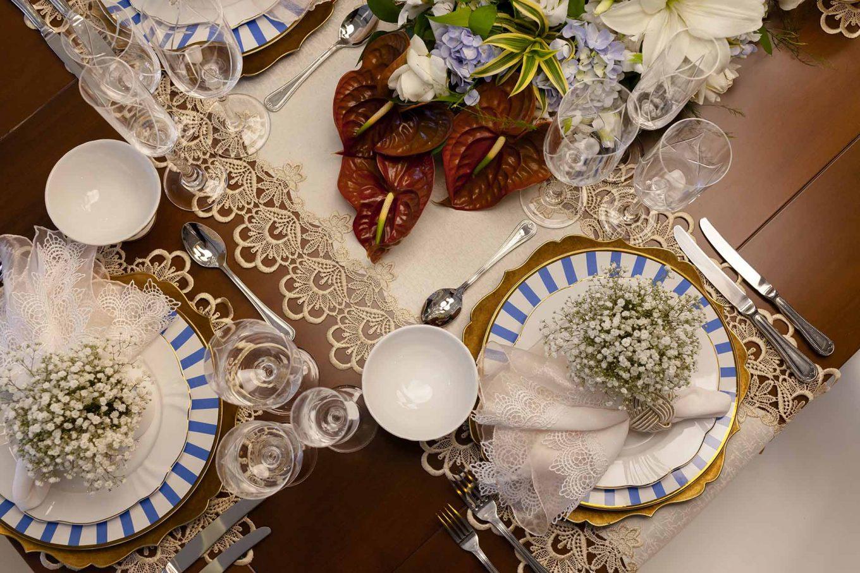 Imagem: Os antúrios bordôs criam pontos de cor na mesa, que contrastam com a neutralidade da decoração e com o azul da louça. Foto: Raphael Günther/Bespoke Content.