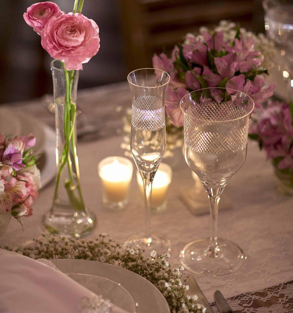 Imagem: A estampa destes pratos da Oxford foi inspirada na renda dos vestidos de noiva e definiu a escolha pelas toalhas de mesa feitas com renda de vestidos, dando ainda mais charme à ambientação. Na mesa dos noivos, eles foram cercados por delicadas flores. Foto: Raphael Günther/Bespoke Content.