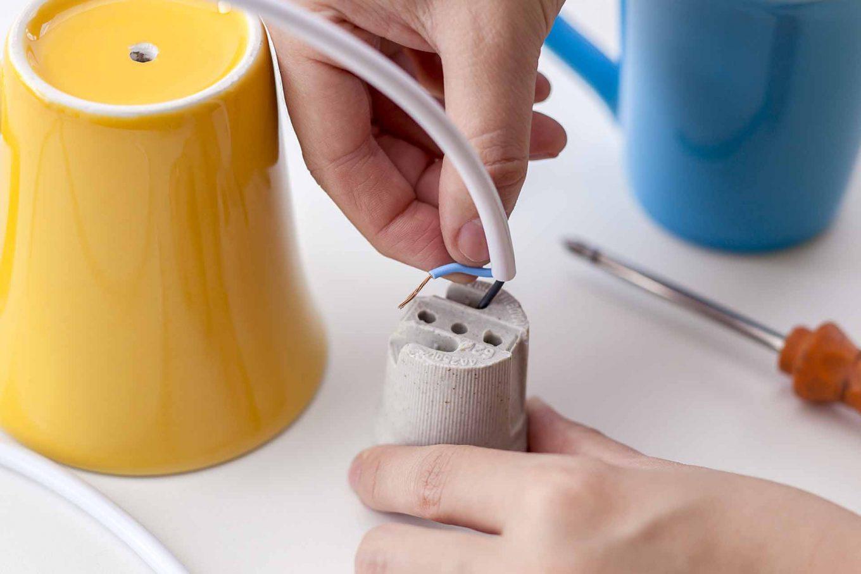 Imagem: Passo 3: Descasque o fio elétrico e faça a conexão com o bocal. Ele será fixado no fundo da caneca com cola epóxi para dar mais firmeza para a lâmpada. Foto: Raphael Günther/Bespoke Content.