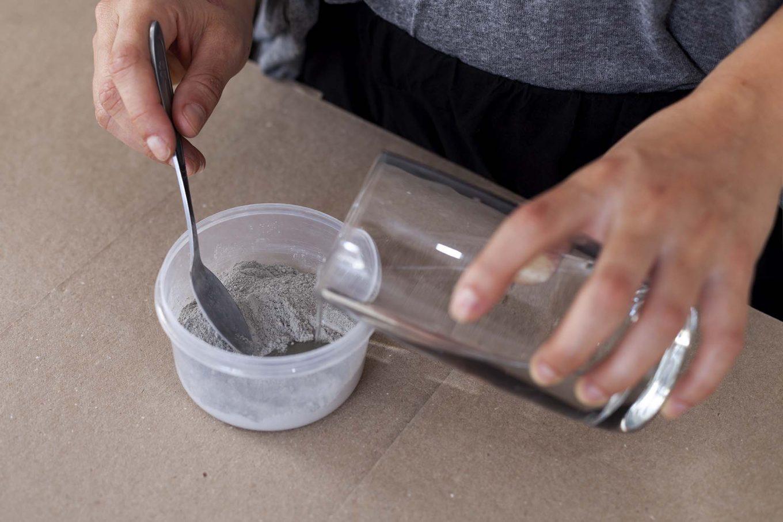 Imagem: Passo 1: Para evitar sujeira, isole o espaço a ser trabalhado com jornal ou algum papelão. Prepare uma mistura de cimento e água que será usada para fixar o galho. Use 1/2 copo de mistura de cimento já pronta e acrescente água até que fique homogêneo, como uma espécie de creme. Foto: Raphael Günther/Bespoke Content.