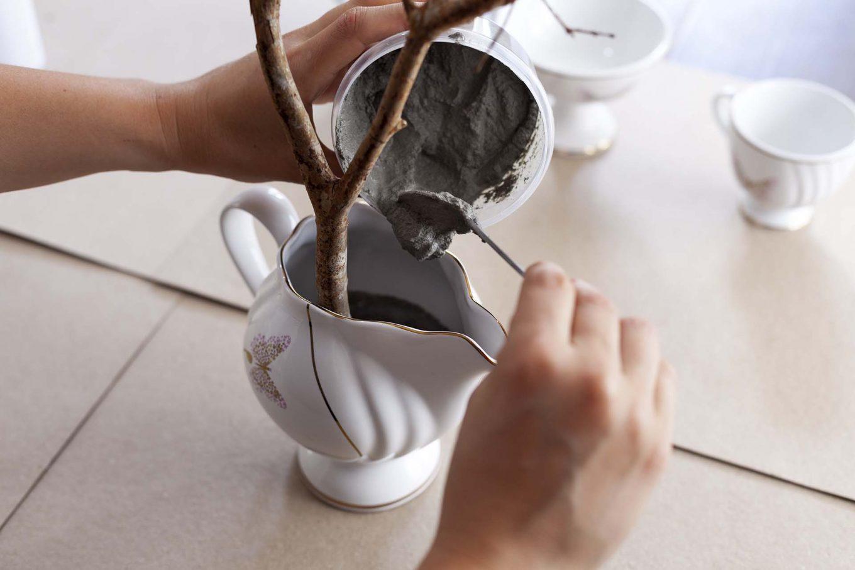 Imagem: Passo 2: Coloque a mistura dentro da leiteira. Posicione o galho e deixe o cimento secar pelas próximas 24 horas. Foto: Raphael Günther/Bespoke Content.