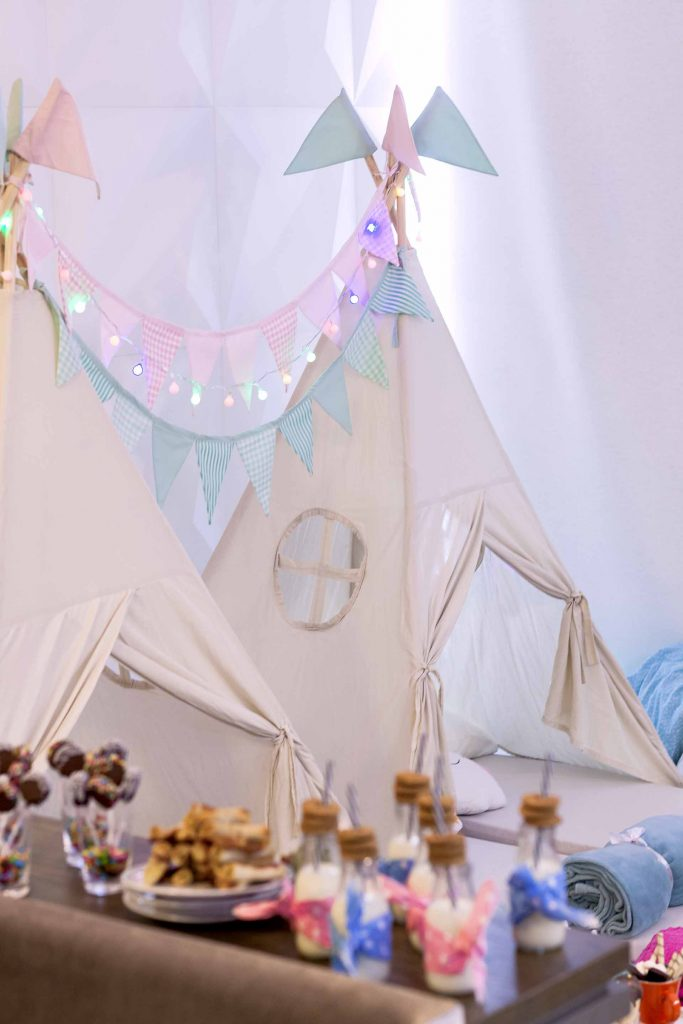 Imagem: Lanternas, bandeirinhas e cabanas em cores delicadas criam um ambiente aconchegante e lúdico, para a criançada fazer a festa. O buffet foi disposto ao lado das cabanas para ficar acessível para todos. No buffet, xícaras de chá serviram como suporte para mais guloseimas. Balas, marshmallows, doces e confeitos de chocolate foram dispostos de forma alegre e divertida. Muitas cores, tanto no cenário quanto na comida, completam a expectativa das crianças para uma festa do pijama. Foto: Raphael Günther/Bespoke Content.