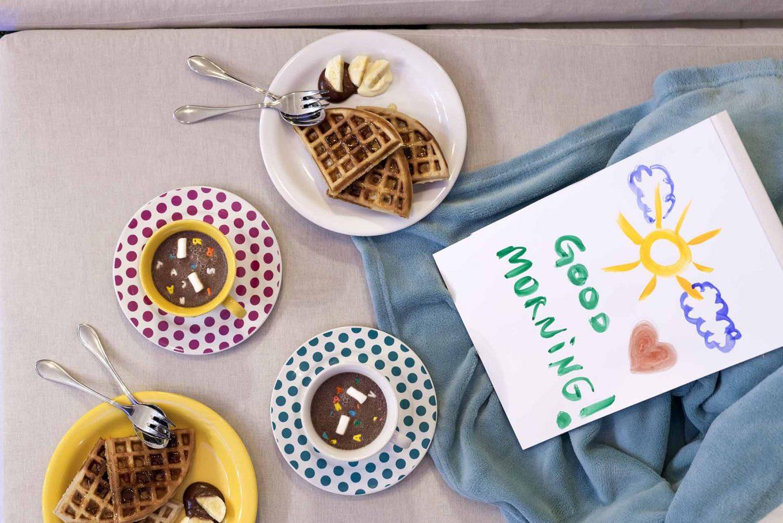 Imagem: Também é preciso lembrar do café da manhã. Para este momento, uma opção tradicional que agrada os pequenos é waffle belga servido com mel, fatias de banana e cobertura de chocolate. Foto: Raphael Günther/Bespoke Content.