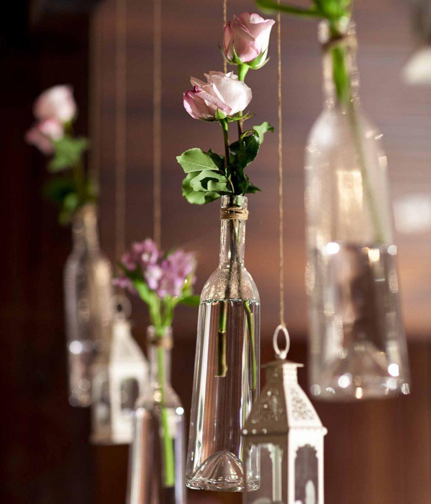Imagem: Para amenizar a estrutura aparente do local, garrafas foram penduradas nas vigas de madeira, compondo com as flores e as lanternas marroquinas. Foto: Raphael Günther/Bespoke Content.