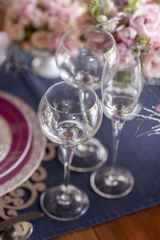 Imagem: Montada em tons de azul, a composição da mesa dá destaque para a louça e detalhes decorativos cor de rosa. Foto: Raphael Günther/Bespoke Content.