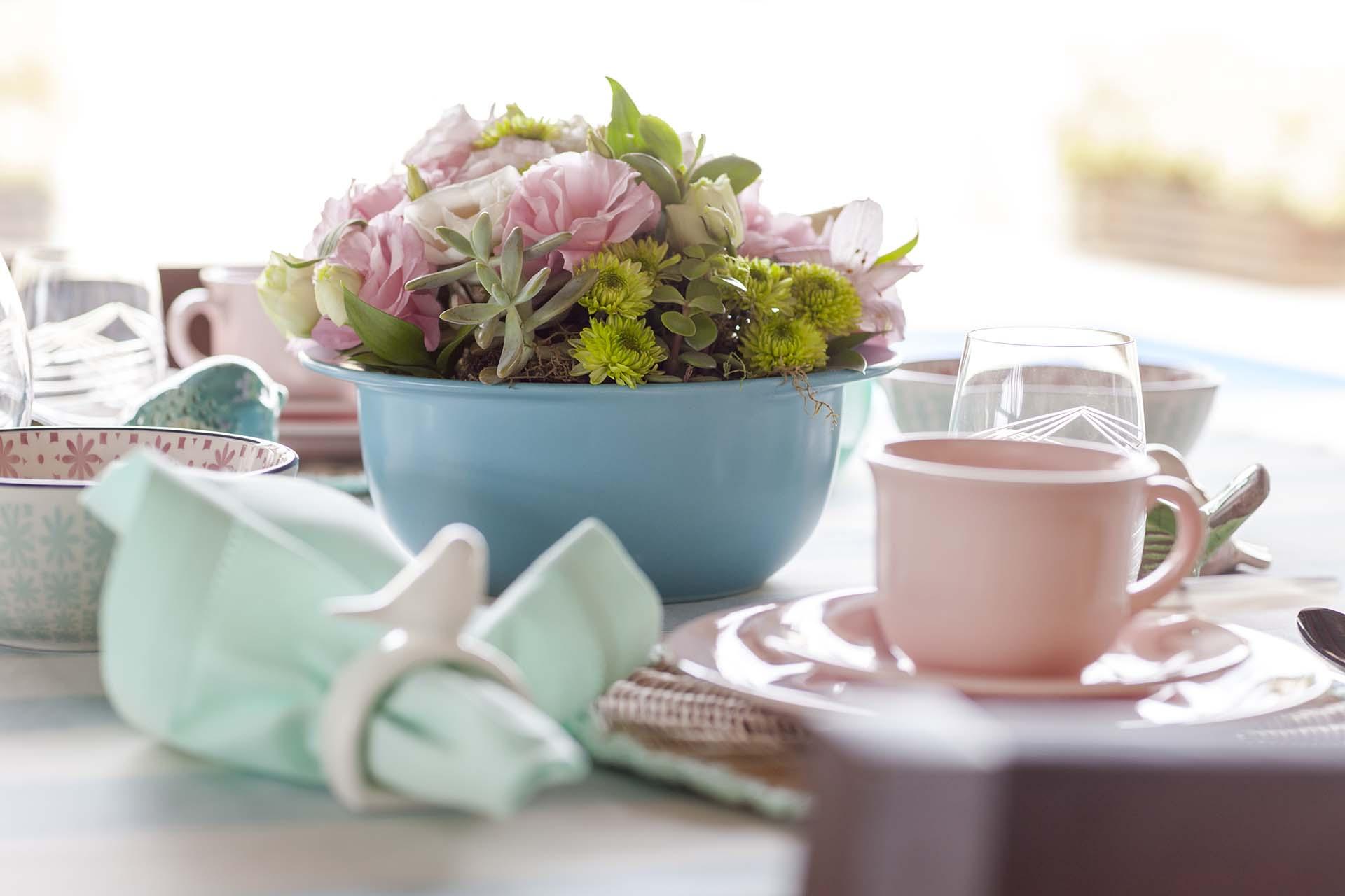 Imagem: A maior descontração desta mesa é o uso da panela azul de cerâmica da Oxford Cookware como vaso. A composição com as flores deixa tudo mais charmoso. Foto: Raphael Günther/Bespoke Content.