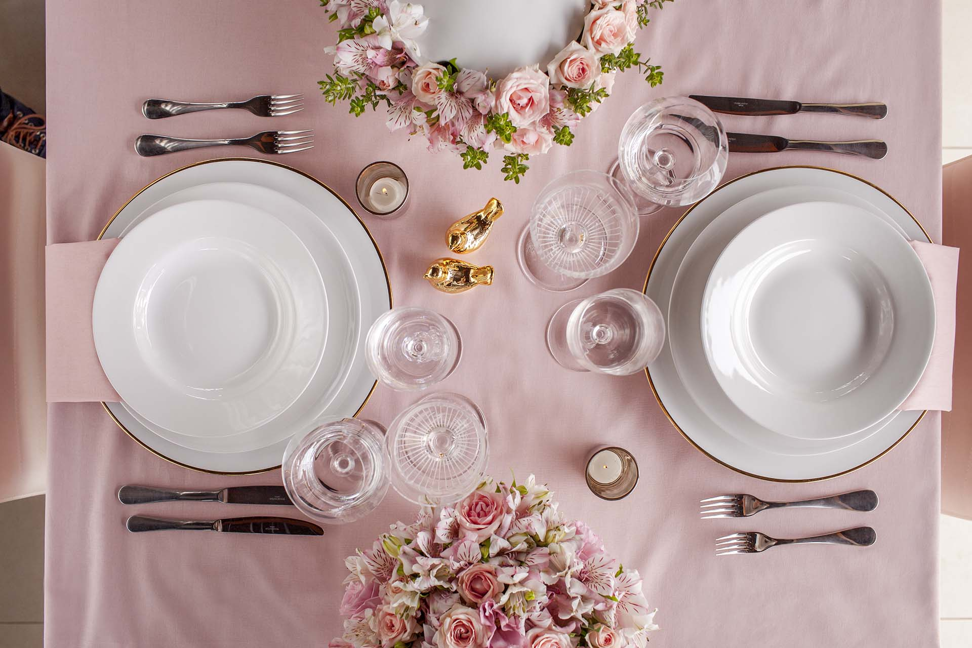 Imagem: Para refinar a louça branca, foi usado um sousplat de porcelana com filete dourado, velas e taças de cristal. Foto: Raphael Günther/Bespoke Content.