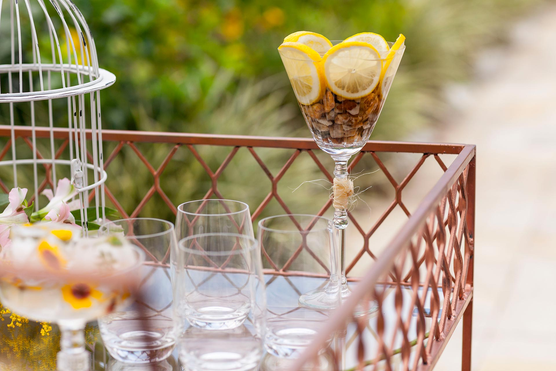 Imagem: A cor cobre em elementos como a mesa de bebidas e os talheres, compõe muito bem com o verde das áreas externas. Foto: Raphael Günther/Bespoke Content.