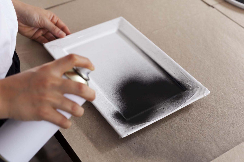 Imagem: Passo 1: Para evitar sujeira, isole o espaço a ser trabalhado com jornal ou algum papelão. Com uma fita, proteja as áreas da travessa que não serão pintadas. Foto: Raphael Günther/Bespoke Content.