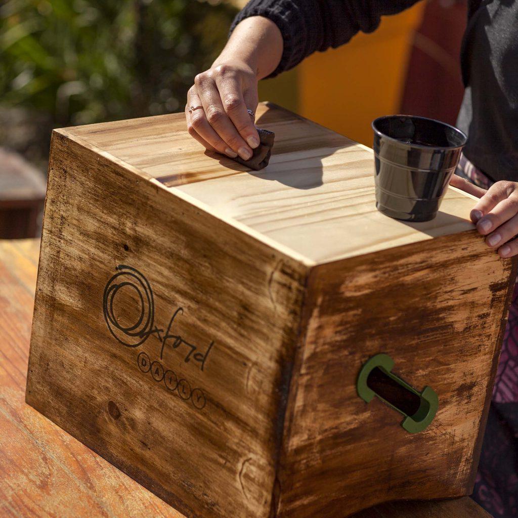 Imagem: Passo 1: Para passar o betume é necessário lixar a superfície do caixote para tirar o brilho do selador. O betume pode ser aplicado com uma trouxinha de pano ao invés de pincel ou rolo. Facilita muito e o acabamento fica bem melhor. Foto: Raphael Günther/Bespoke Content.