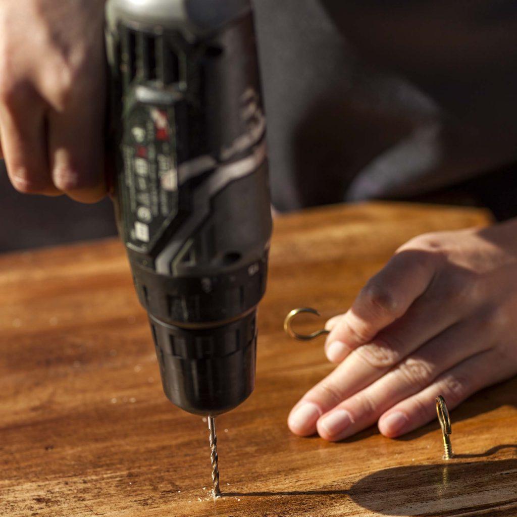 Imagem: Passo 4: Na parte inferior da caixa, fixe os ganchos onde serão penduradas as xícaras. Para facilitar a colocação dos ganchos, faça um pequeno furo (superficial) com uma broca menor (a de 3 mm) e depois fixe-os com a mão. Certifique-se de que estão bem presos. Foto: Raphael Günther/Bespoke Content.
