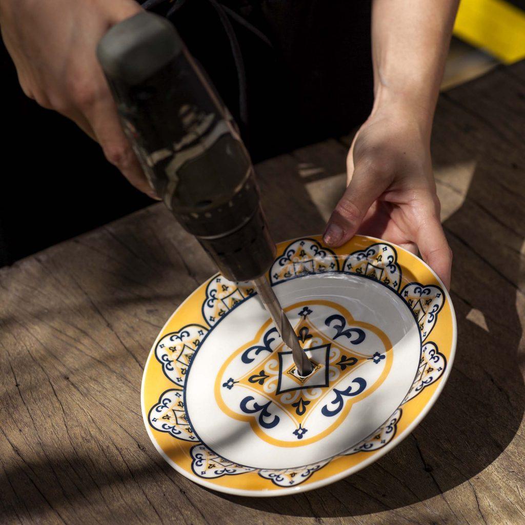 Imagem: Passo 2: Enquanto a tinta seca, fure as louças com a broca de videa 10mm. Utilize água para perfurar as louças, pois isso facilita muito e não deixa que o impacto quebre a peça. Se você usar uma furadeira de mão, peça a ajuda de outra pessoa, pois é necessário um pouco mais de força. Foto: Raphael Günther/Bespoke Content.
