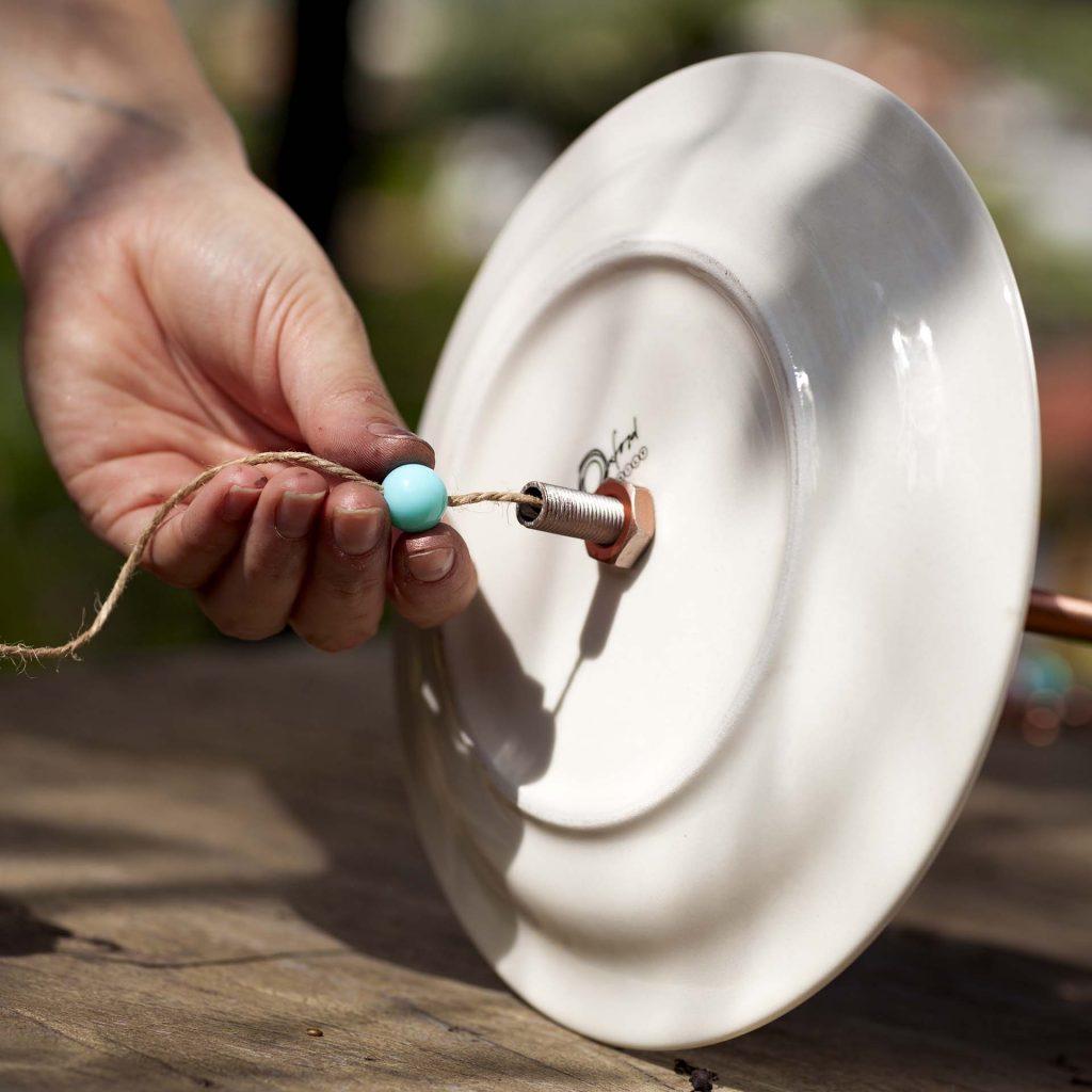 Imagem: Passo 6: Para pendurar o comedouro, utilize a corda de sisal passando por entre o tubo (use um arame para puxar o fio). Para que as pontas fiquem fixas, use uma miçanga nas duas pontas do tubo. Foto: Raphael Günther/Bespoke Content.