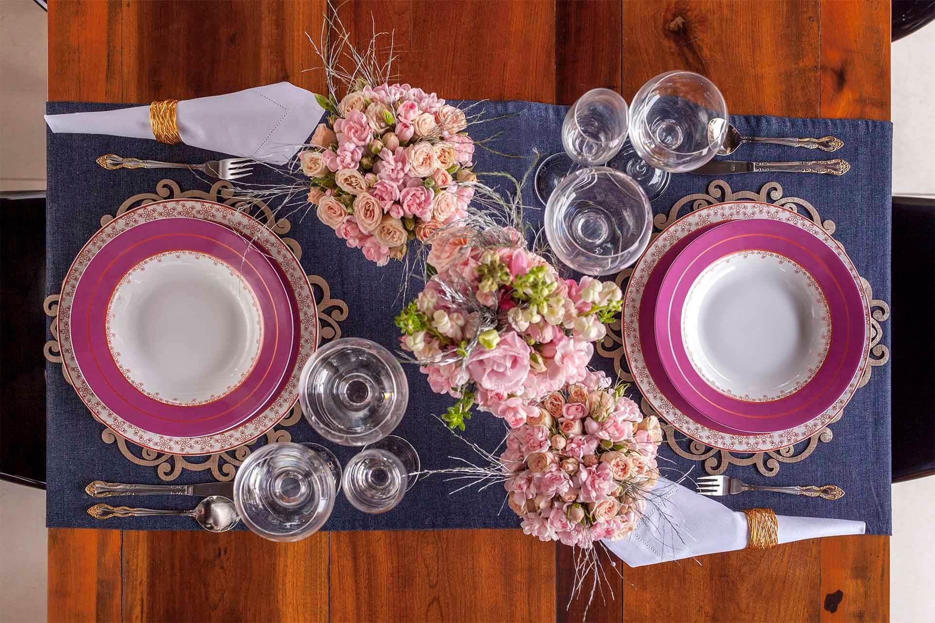 Imagem: Uma mesa que une elegância, garantida pelo guardanapo de linho branco envolto em dourado, e descontração, pela escolha do jeans. Foto: Raphael Günther/Bespoke Content.