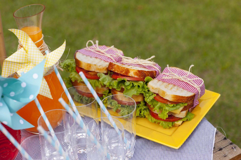 Imagem: Os pratos coloridos da linha Plateau acomodam os sandubas, bem recheados e decorados. É só desamarrar e usar o tecido como guardanapo! Foto: Raphael Günther/Bespoke Content.