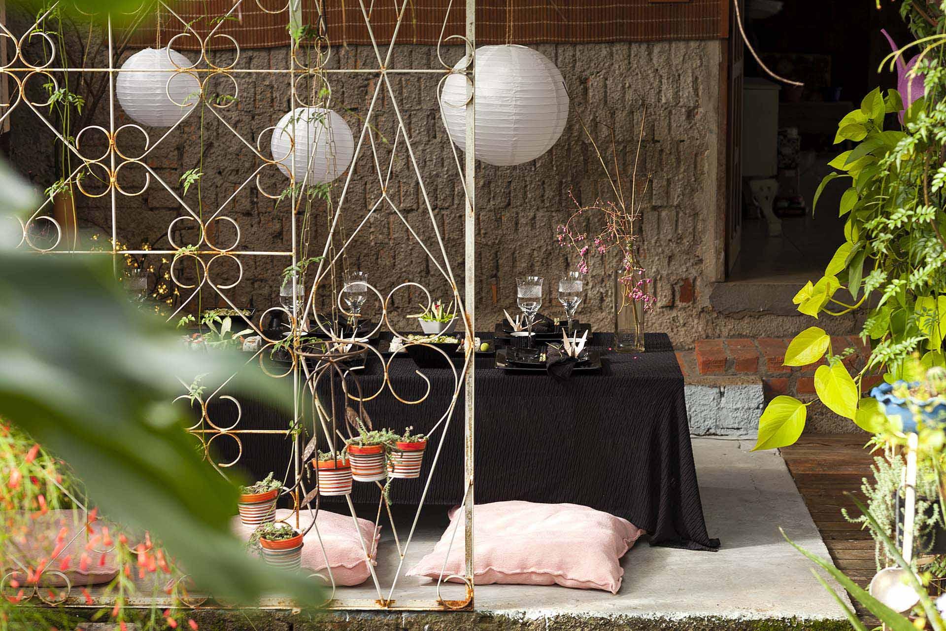 Imagem: Luminárias, almofadas e bastante verde criam um clima bem aconchegante e convidativo para passar longas horas entre amigos. Foto: Raphael Günther/Bespoke Content.