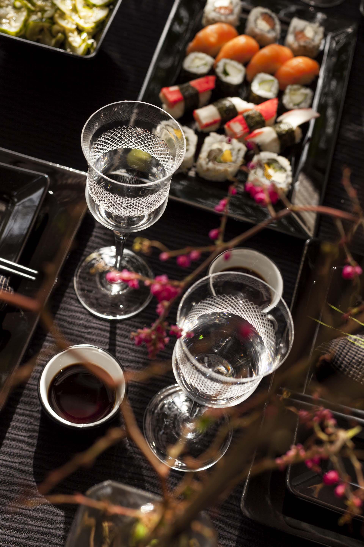 Imagem: A transparência dos cristais é um destaque e charme à parte no meio de todo o preto. Dão elegância à mesa deixando a comida permanecer como elemento principal. Foto: Raphael Günther/Bespoke Content.