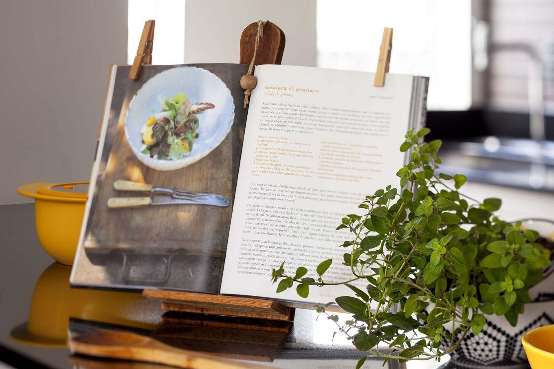 Imagem: Agora que o livro de receitas está seguro, mantenha o suporte sempre por perto, ele também é um item lindo de decoração na cozinha. Aproveite grampos de roupas para segurar as páginas em uso. Foto: Raphael Günther/Bespoke Content.