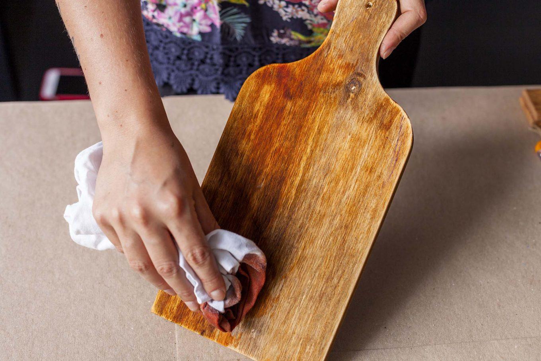 Imagem: Passo 2: Com a ajuda de um pedaço de pano, passe a anilina diluída na tábua de corte e nos pedaços de madeira já cortados na largura da tábua. Se quiser uma cor mais intensa, aumente a quantidade de anilina a ser diluída no álcool. Foto: Raphael Günther/Bespoke Content.