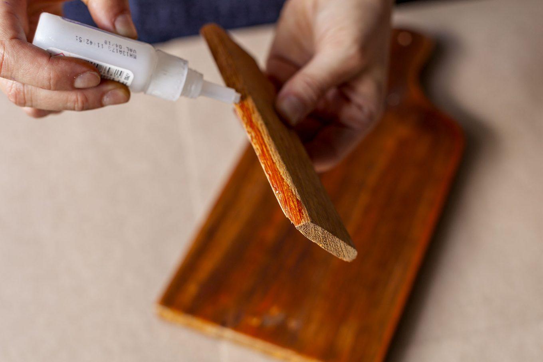 Imagem: Passo 3: Com a cola instantânea, cole um dos pedaços de madeira na base inferior da tábua. Ele vai servir para segurar e apoiar o livro. Foto: Raphael Günther/Bespoke Content.