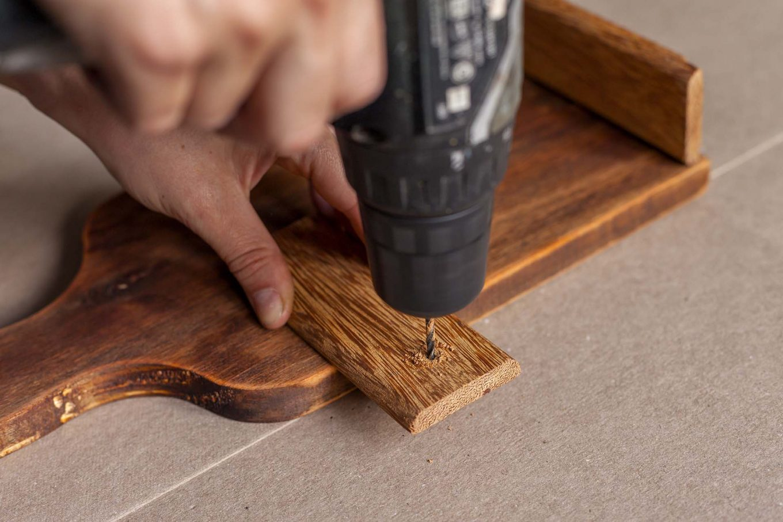 Imagem: Passo 4: O outro pedaço de madeira vai servir para deixar a tábua em pé. Para isso, utilize uma parafusadeira ou uma chave de fenda para perfurar a ponta desse pedaço de madeira. Foto: Raphael Günther/Bespoke Content.