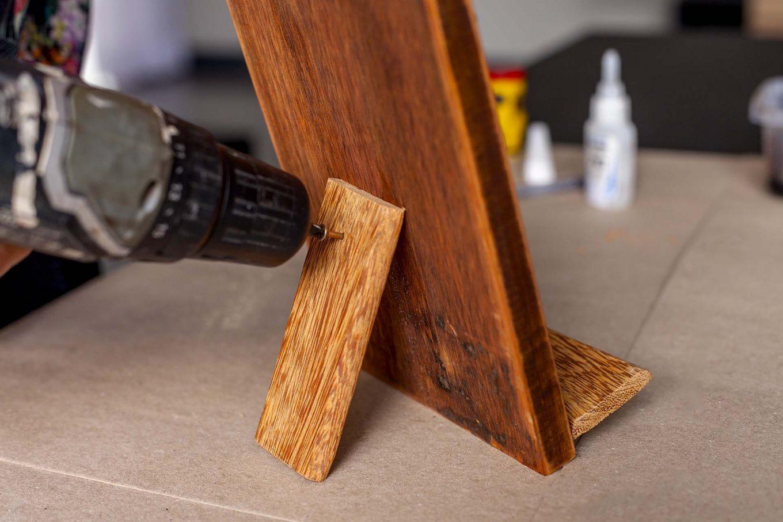 Imagem: Passo 5: Ainda com a parafusadeira, faça a fixação da madeira na parte de trás do suporte. Foto: Raphael Günther/Bespoke Content.