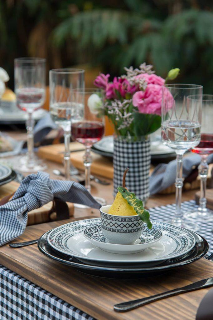 Imagem: A mesa posta em preto e branco é linda e atemporal. A dupla de cores aparece nas louças, no caminho de mesa, nos guardanapos e nos vasos. Foto: Cacá Bratke.