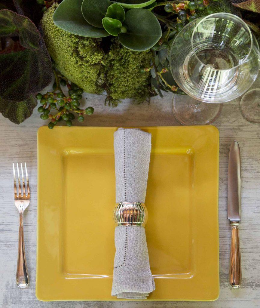 Imagem: A louça amarela leva um toque de cor e de luz para a mesa. Um guardanapo de cor discreta e talheres levemente brilhantes deixam a composição elegante na medida certa. Foto: Julia Ribeiro.
