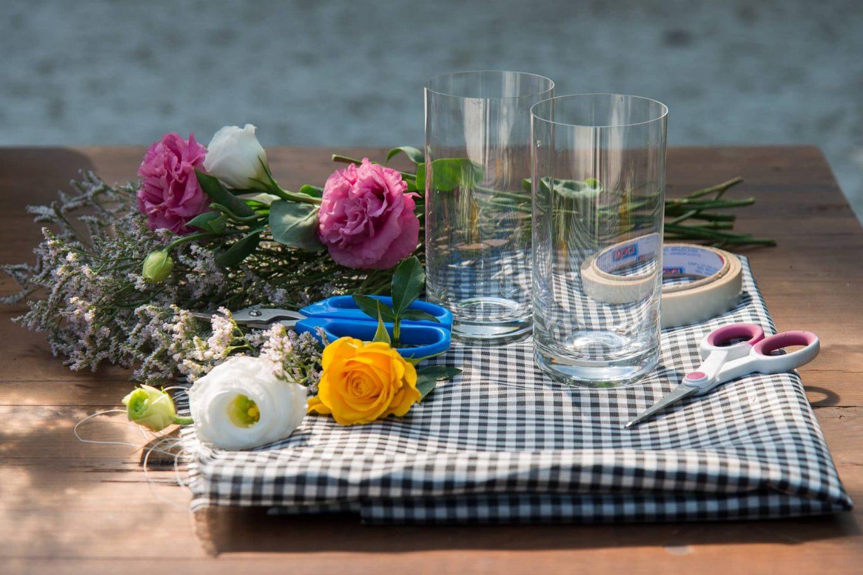 Imagem: Flores sortidas, um retalho de tecido, tesoura, fita dupla face. E copos de long drink da Oxford Crystal que fazem as vezes de vaso. É tudo o que você precisa para este tutorial de DIY. Foto Cacá Bratke.